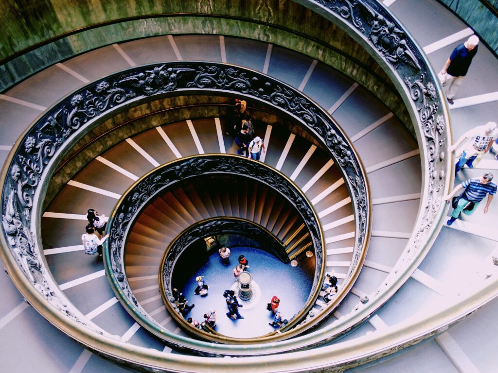 the spiral stairs leading downward at the Vatican Museums in Rome